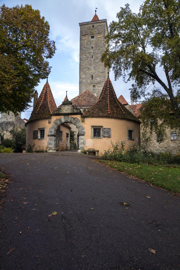 Una strada che conduce al portone della città in una vecchia costruzione con l'arco di pietra nel der Tauber del ob di Rothenburg immagini stock