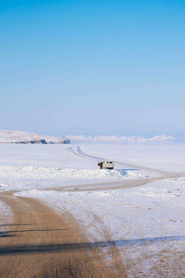 Una strada non asfaltata ad un lago congelato Strada congelata Snowy su un lago La montagna è davanti alla strada ghiacciata fotografia stock
