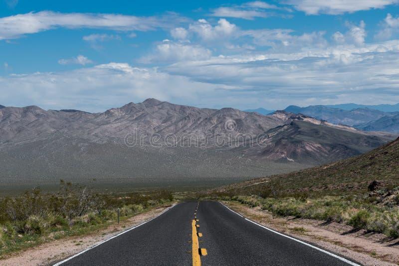 Una strada principale che retrocede alla prospettiva verso una catena montuosa in un paesaggio del deserto fotografia stock