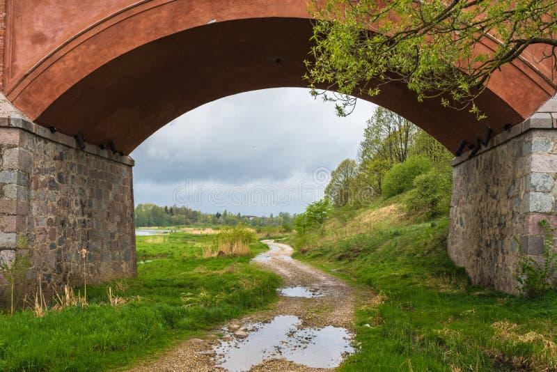 Una strada rurale della ghiaia con le pozze fotografia stock