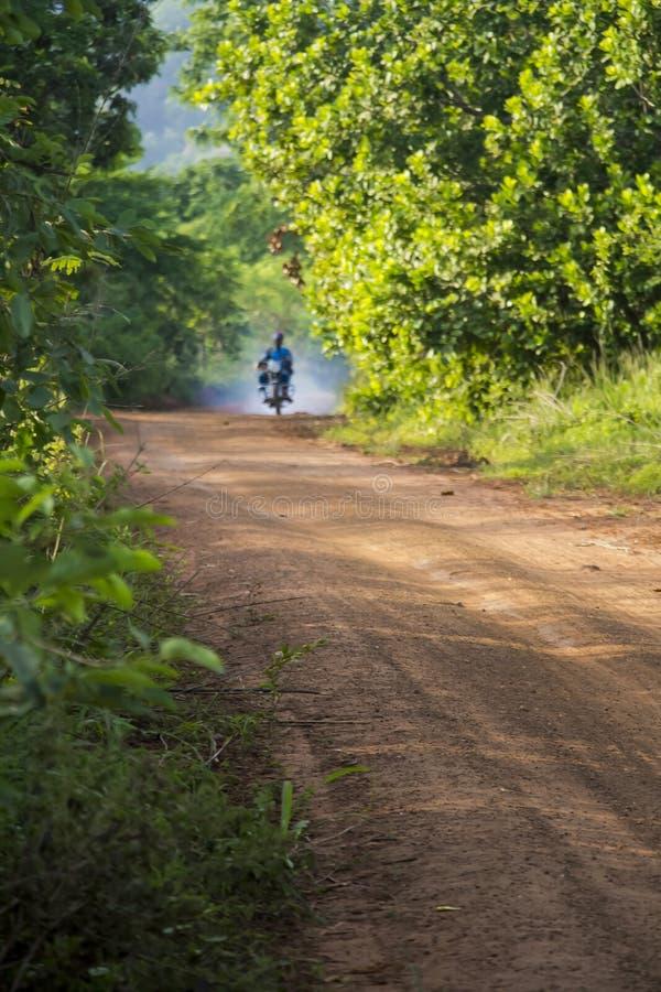 Una strada rurale untarred con il motociclo fumoso fotografia stock libera da diritti