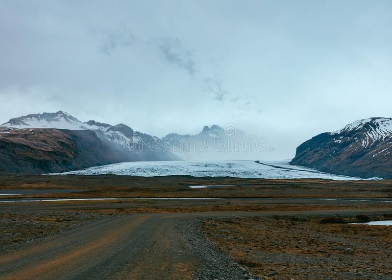 Una strada stretta in un deserto con le belle colline e montagne nei precedenti fotografia stock libera da diritti