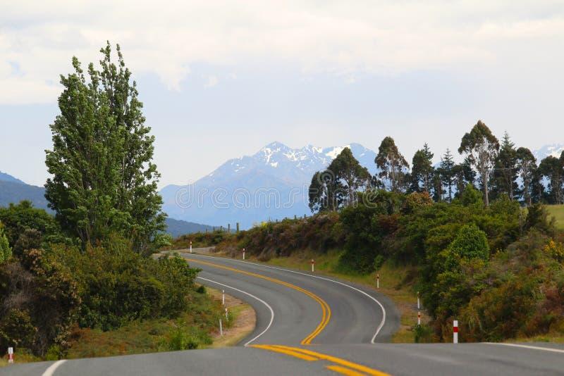 Una strada sull'isola del sud della Nuova Zelanda con il landscap selvaggio tipico immagini stock