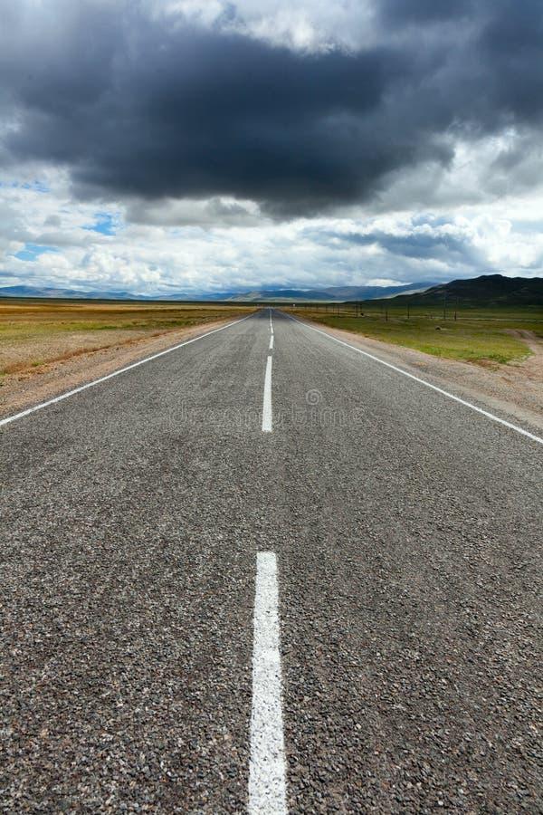 Una strada vuota del deserto con le nuvole di presentimento e scure di tempesta fotografie stock libere da diritti