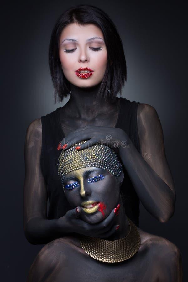 Una strega di due ragazze in pittura nera con gli ornamenti dell'oro fotografia stock libera da diritti