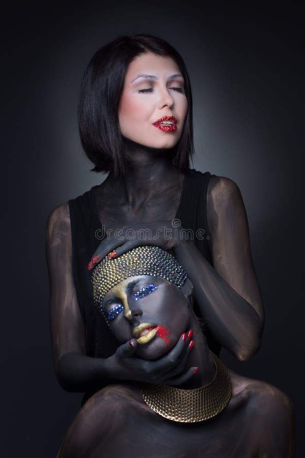 Una strega di due ragazze in pittura nera con gli ornamenti dell'oro immagini stock libere da diritti