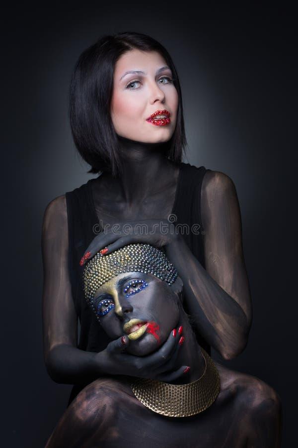 Una strega di due ragazze in pittura nera con gli ornamenti dell'oro immagine stock