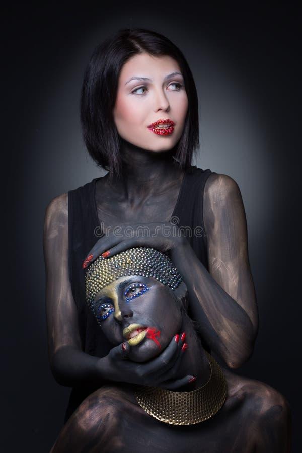 Una strega di due ragazze in pittura nera con gli ornamenti dell'oro fotografia stock