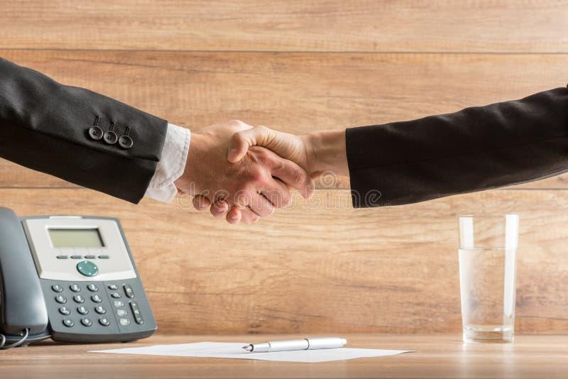 Una stretta di mano di due soci commerciali dopo una riuscita riunione a fotografia stock libera da diritti
