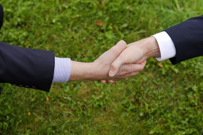 Una stretta di mano di due uomini d'affari in vestiti immagini stock