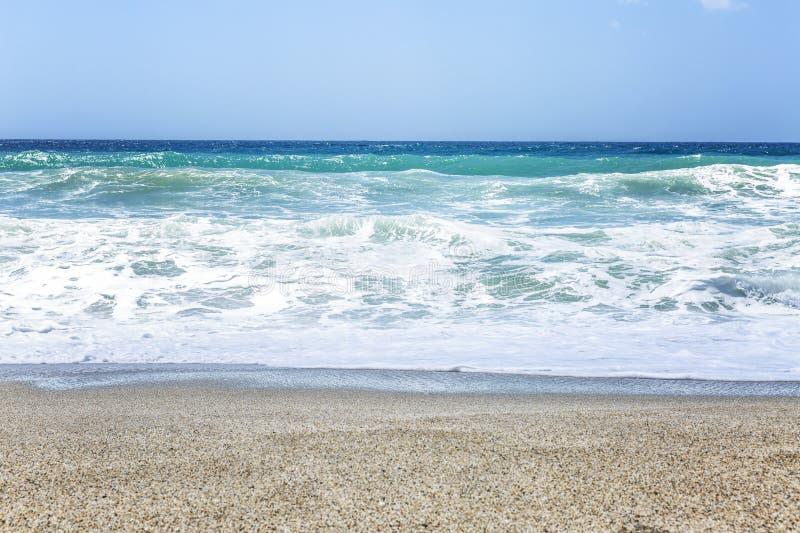 Una striscia della spiaggia sabbiosa con il mare ed il cielo blu del turchese Bello paesaggio fotografie stock libere da diritti