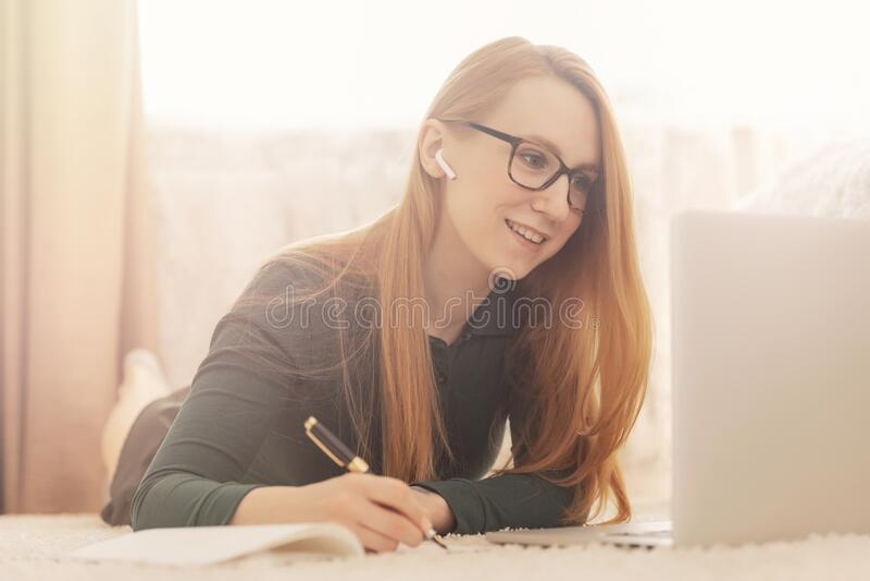 Una studentessa freelancer lavora al computer online dalla sua camera da letto fotografie stock