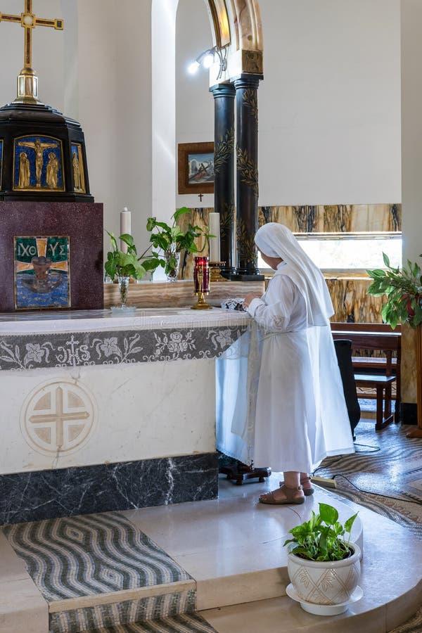 Una suora del monaco in abiti bianchi prega nel corridoio centrale del monastero di beatitudine situato sulla montagna sulla cost fotografia stock