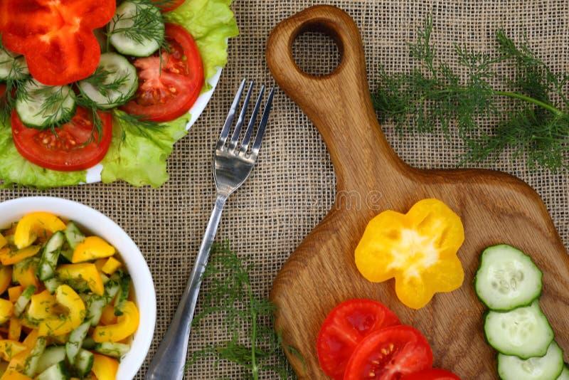 Una tabla de cortar con las rebanadas de tomates, pepinos y pimienta, una bifurcación y dos placas de las ensaladas vegetales imágenes de archivo libres de regalías