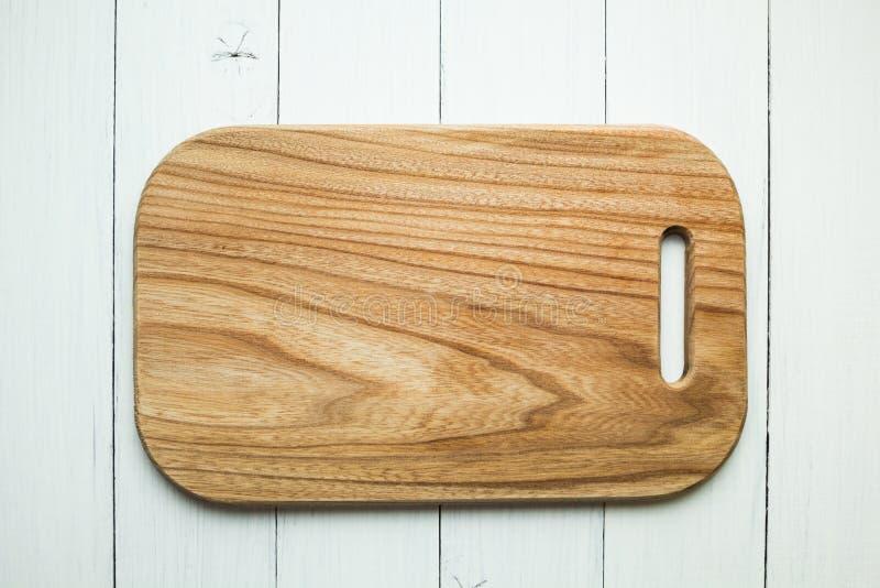 Una tabla de cortar de madera vac?a con una textura de madera en un fondo blanco de la tabla Visi?n superior fotos de archivo