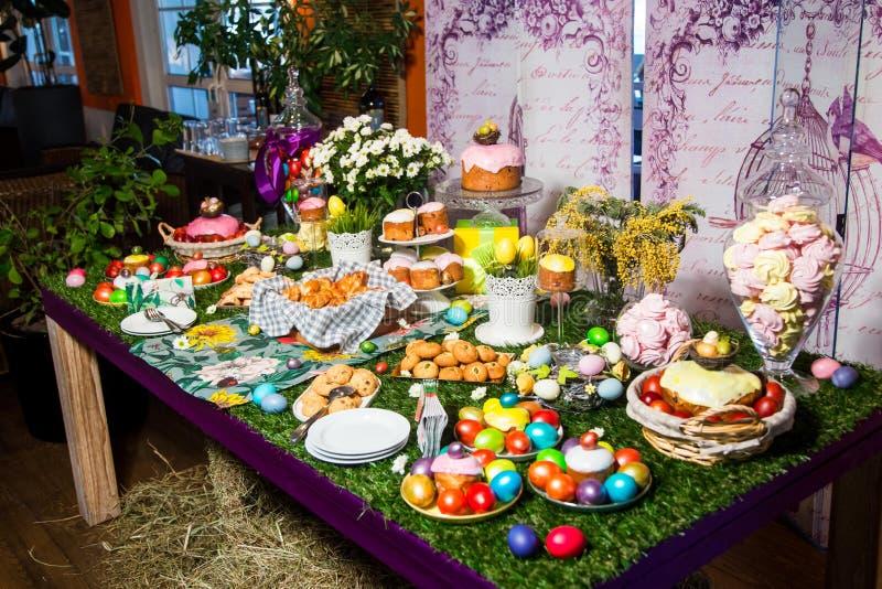 Una tabla de madera con un mantel herboso y las invitaciones de Pascua: huevos, tortas, huevos de chocolate, merengues fotografía de archivo libre de regalías