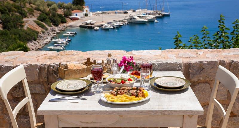 Una tabla sirvió para dos con souvlaki y las patatas fritas del pollo, la ensalada griega, los bocados y las bebidas en la terraz imágenes de archivo libres de regalías