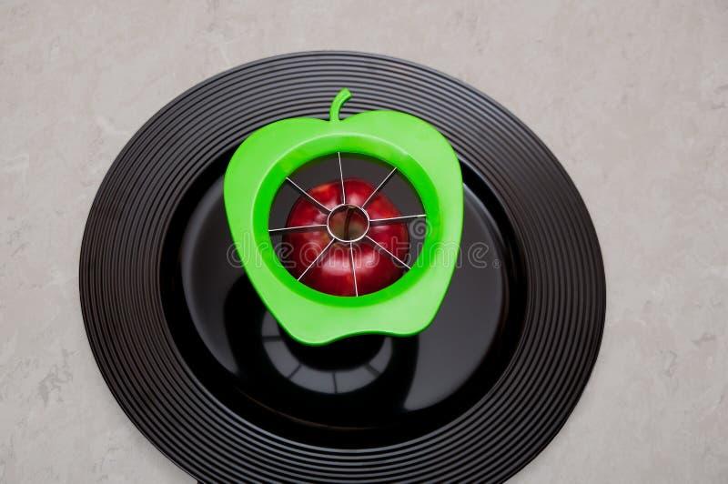 Una taglierina moderna verde della mela con una mela sana organica e rossa in pieno delle vitamine naturali e nutrizione su un pi fotografie stock libere da diritti