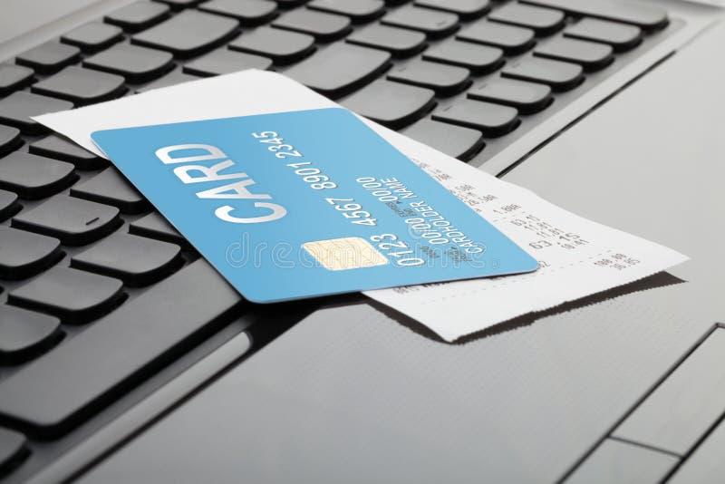 Una tarjeta de crédito y un recibo sobre el teclado de ordenador como símbolo de las compras en línea foto de archivo