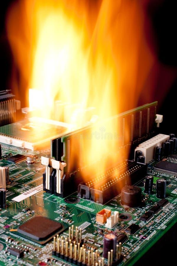 Una tarjeta de madre electrónica del ordenador en el fuego imagen de archivo