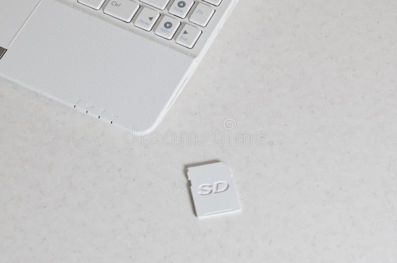 Una tarjeta de memoria SD compacta miente en un netbook blanco El dispositivo de almacenamiento de la información digital es pron fotos de archivo libres de regalías