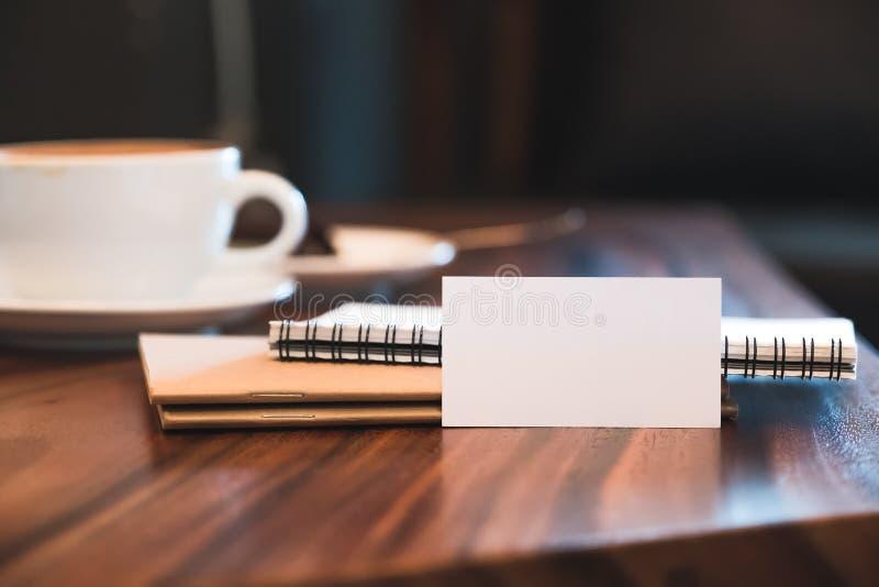 Una tarjeta de visita en blanco blanca con los cuadernos y la taza de café en la tabla de madera del vintage fotografía de archivo
