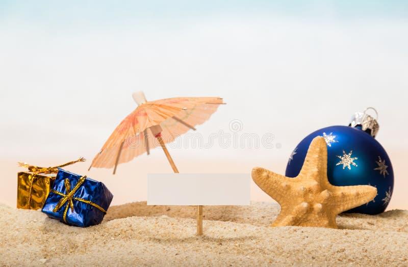 Una tarjeta en blanco en clavija, un paraguas, la bola y los regalos, estrella de la Navidad imágenes de archivo libres de regalías
