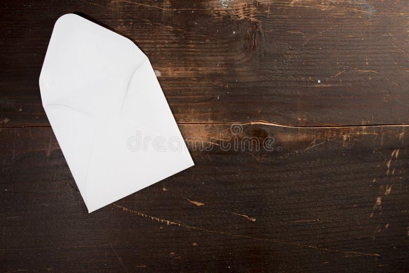 Una tarjeta vacía en blanco envuelve en un fondo de madera de la tabla imagen de archivo libre de regalías