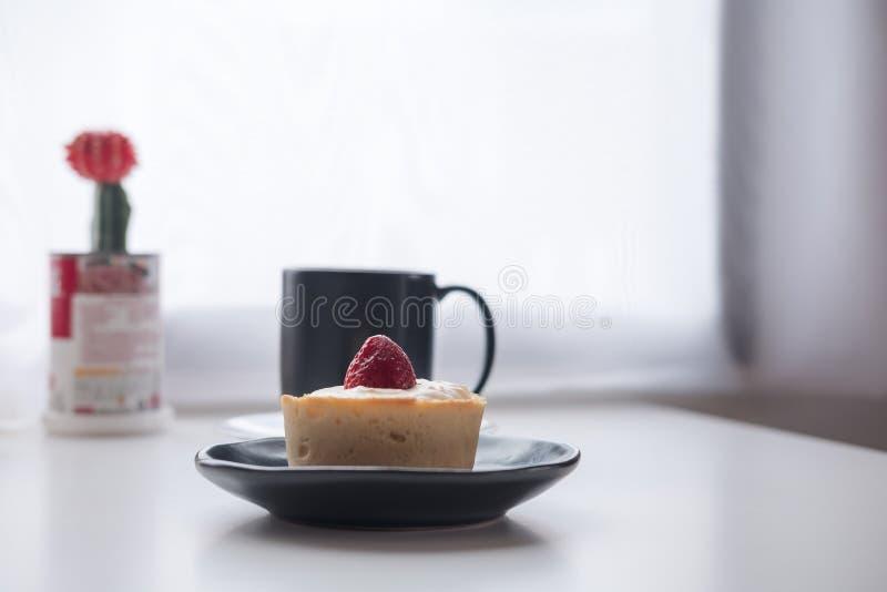 Una tarta del queso de la fresa, una taza negra de café caliente y cactus en fondo de madera de la tabla y de la cortina del vint imagen de archivo libre de regalías