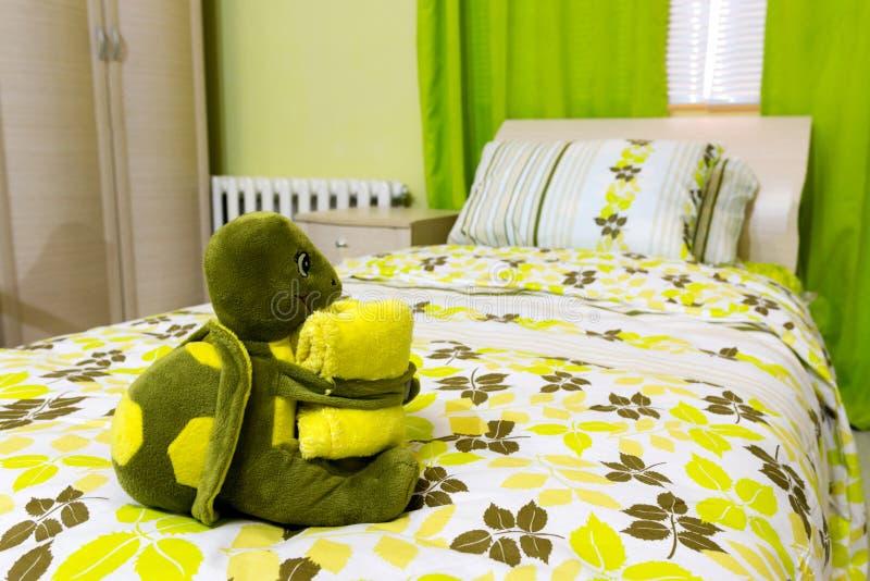 Una tartaruga molle del giocattolo con un asciugamano sul letto fotografia stock