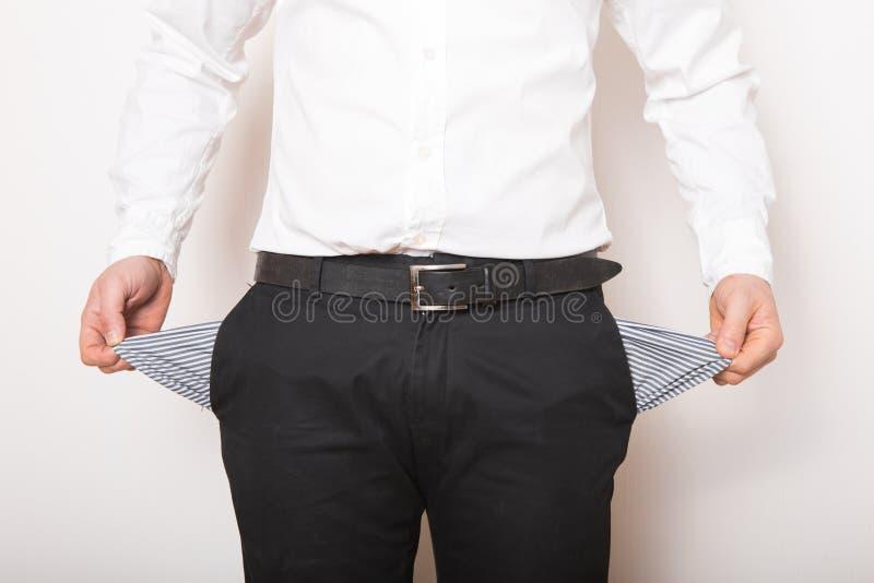 Una tasca vuota nelle mani dell'uomo Broke, concetto di fallimento immagine stock
