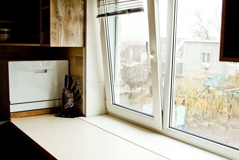 Una tavola di spezzettamento con un insieme dei coltelli nella cucina contro lo sfondo della finestra posto di lavoro pulito per  immagini stock