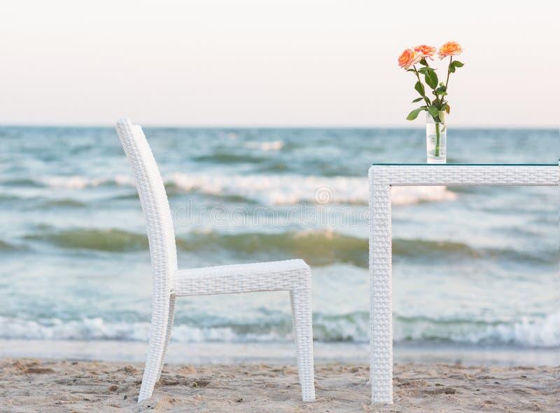 Una tavola e su un vaso con le rose rosa e una sedia comoda su un bello fondo del mare Atmosfera romantica alla spiaggia fotografia stock libera da diritti