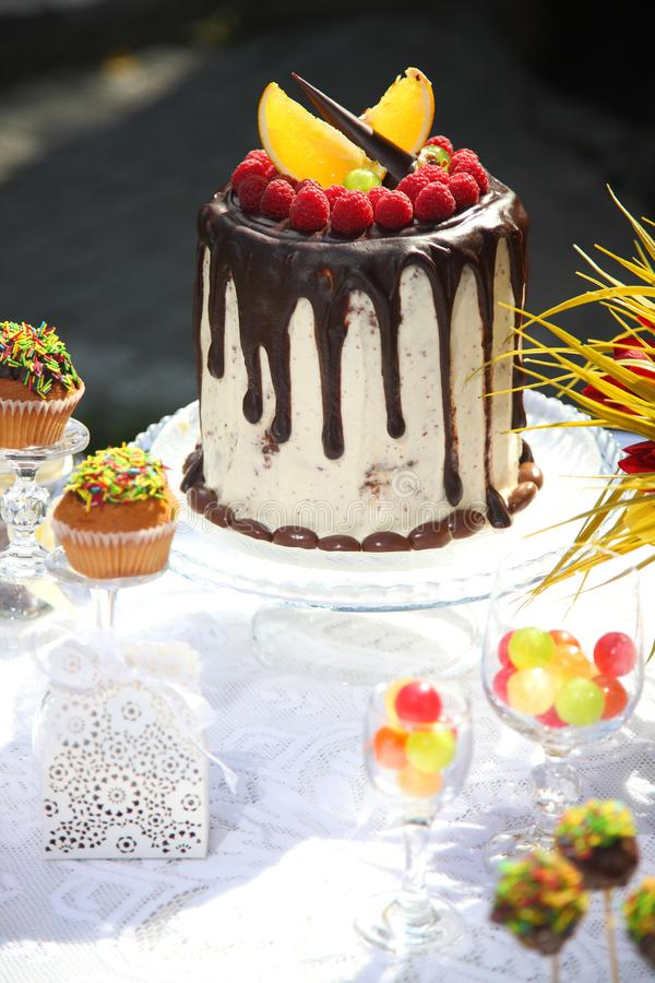 Una tavola festiva decorata con la torta di compleanno con i fiori ed i dolci fotografia stock libera da diritti