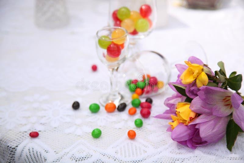 Una tavola festiva decorata con la torta di compleanno con i fiori ed i dolci immagine stock