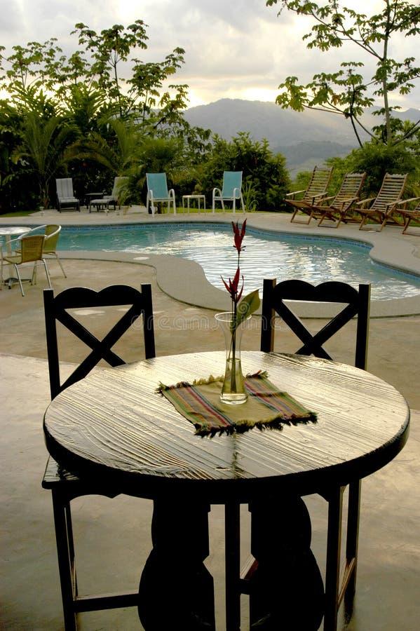 Una tavola per due ad una regolazione del poolside nei tropici di Costa Rica immagine stock