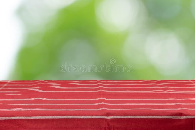 Una tavola vuota con una tovaglia a strisce rossa e un natura verde fotografie stock libere da diritti