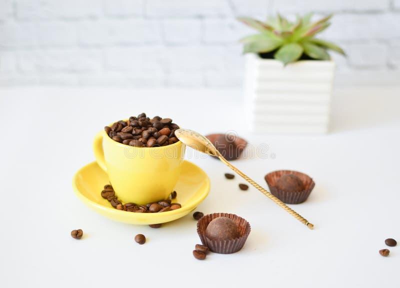 Una taza amarilla con los granos de café naturales, en un fondo blanco, y chocolates Cuchara del vinilo Concepto de caf? de la ma fotografía de archivo