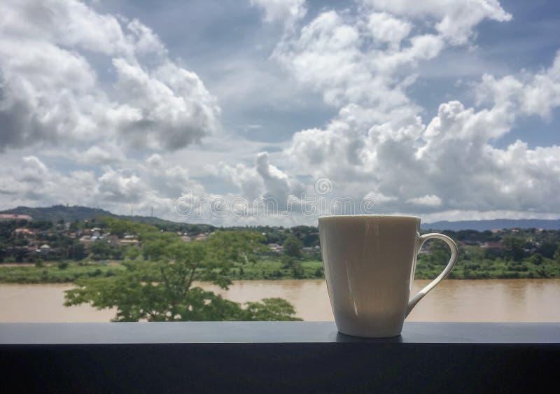 Una taza blanca de café caliente en terraza delante del fondo grande del río imágenes de archivo libres de regalías