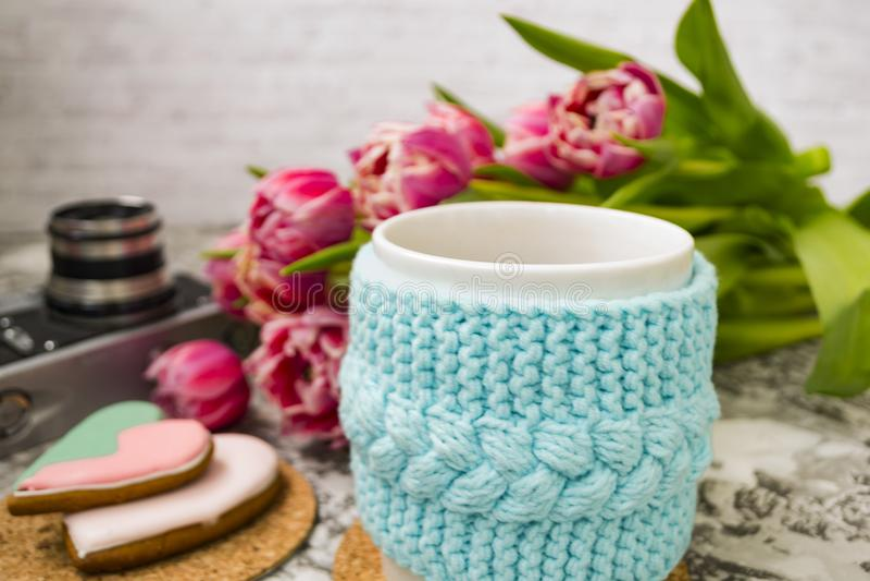 Una taza blanca de té en una caja azul hecha punto con una cámara vieja y tulipanes y dulces rosados, pan de jengibre de las flor imagen de archivo libre de regalías