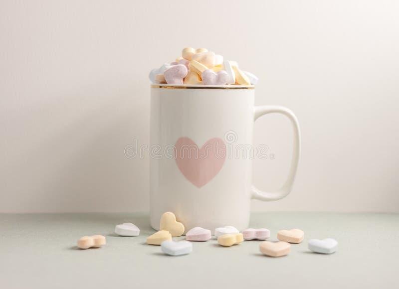 Una taza blanca llena de corazones del caramelo imagen de archivo libre de regalías