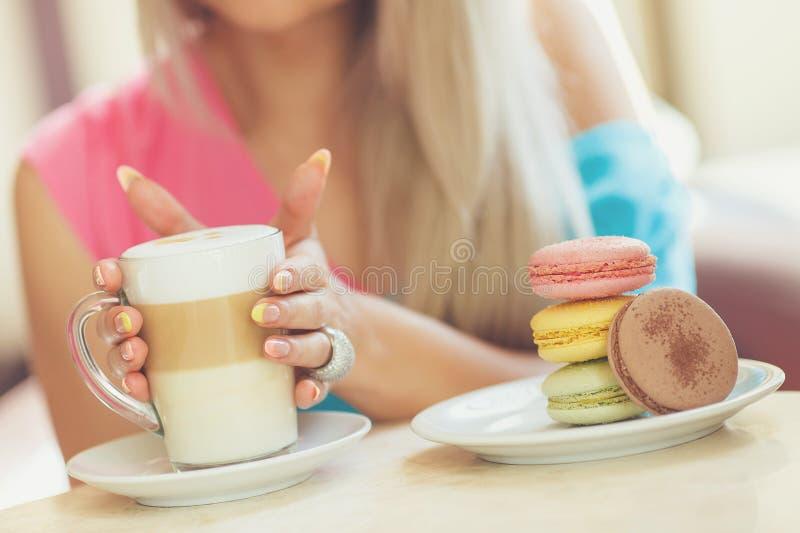 Una taza caliente de latte del café con las galletas coloridas fotografía de archivo libre de regalías