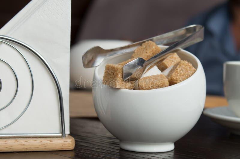 Una taza con los cubos del azúcar de caña, de las azúcar-pinzas y de las servilletas blancos Citas de la atmósfera y de tabla en  imagen de archivo