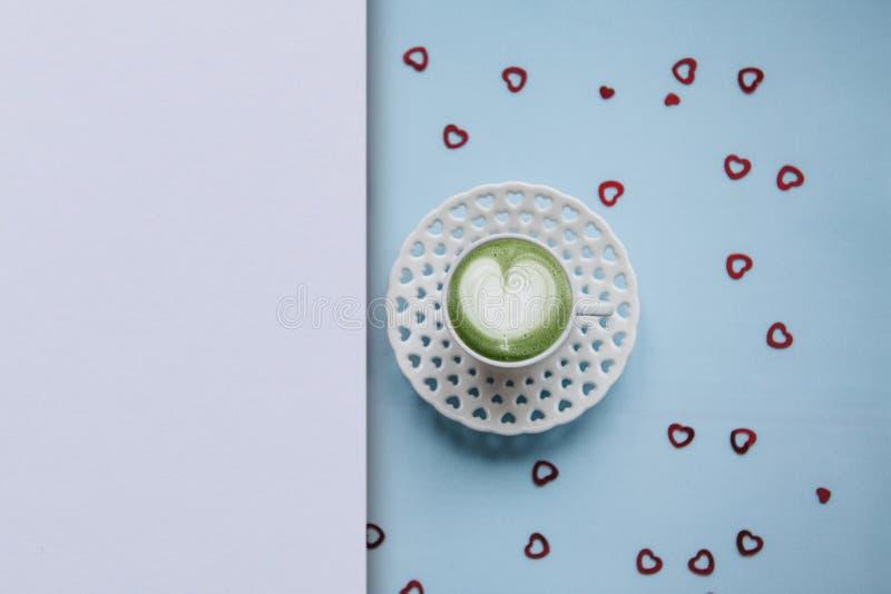 Una taza con un café sabroso y aromático del latte del matcha de la mañana en un fondo festivo fotos de archivo libres de regalías