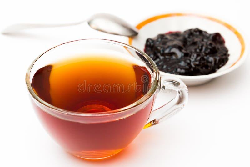 Una taza de atasco del té y del ciruelo fotografía de archivo