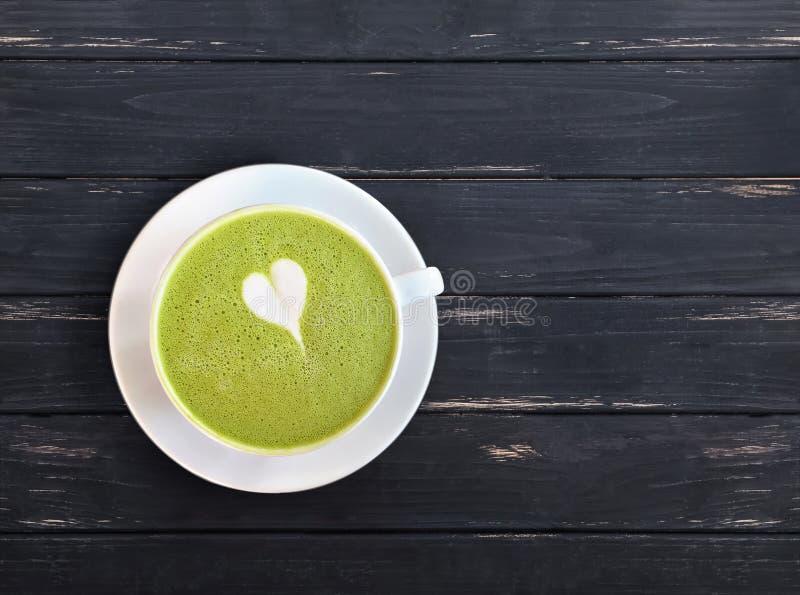 Una taza de bebida del latte del matcha con el pequeño corazón exhausto en la tabla de madera negra imagen de archivo