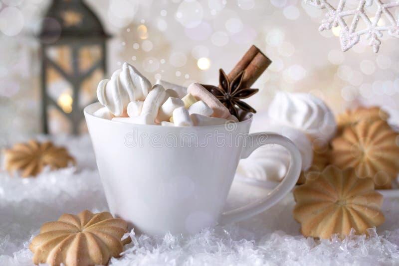 Una taza de cacao caliente con la melcocha o el café con canela y galletas dulces en fondo de la nieve imagen de archivo libre de regalías