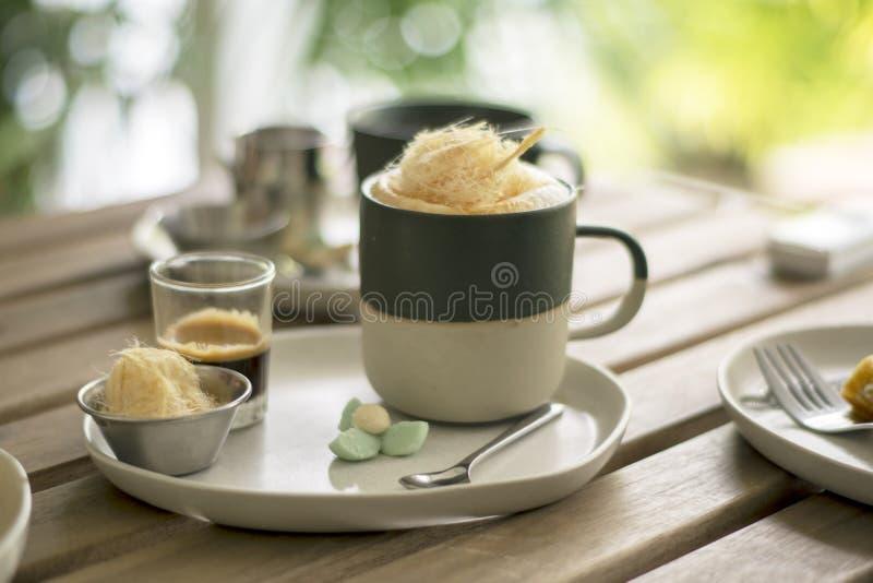 Una taza de café caliente con el tiro, el caramelo de algodón adicionales del azúcar y con bocados tradicionales tailandeses foto de archivo