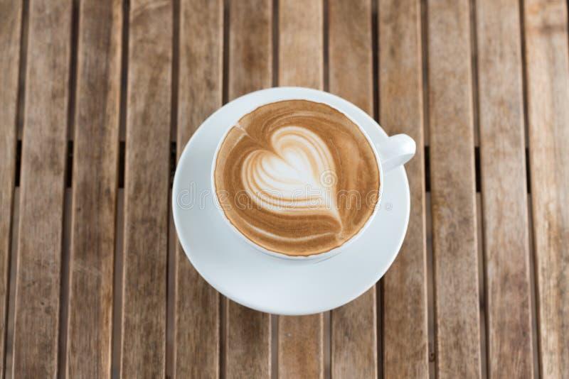 Una taza de café caliente con forma del corazón de la espuma de la leche en una tabla rústica imagenes de archivo