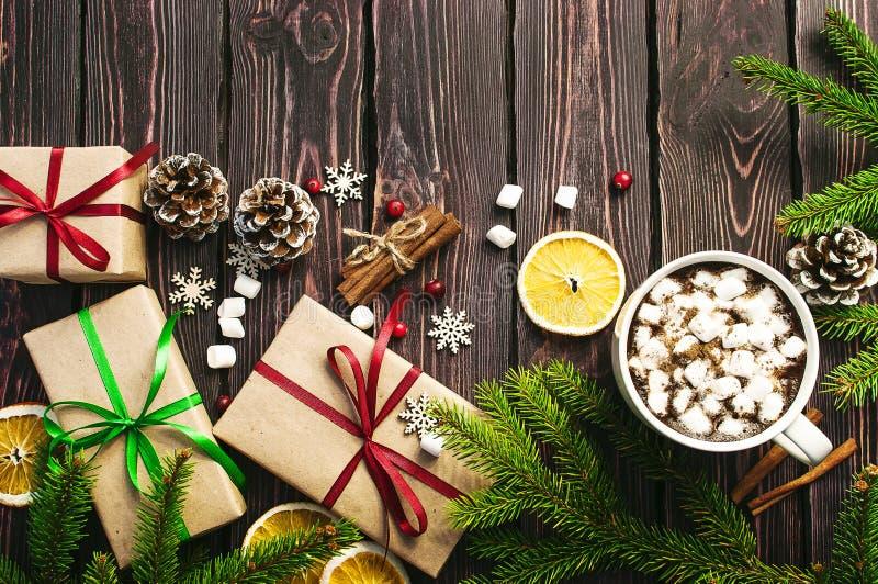 Una taza de café caliente con la melcocha, ramas spruce, conos, regalos de la Navidad, tazas de naranja, copos de nieve, canela,  fotografía de archivo